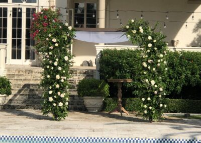 Dark wood chuppah with green floral legs at John Lennon Home Palm beach