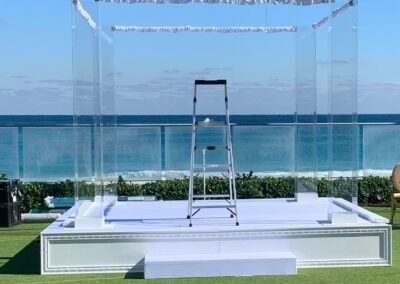 12 x 12 Stage Covered in White fabric with added wood trim front of stage cover